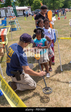 Detroit, Michigan - FBI agents showed children how to use the metal detection equipment that the FBI uses at crime scenes. Children searched for coins - Stock Photo
