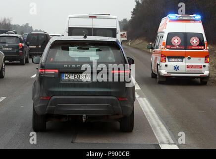 Nuremberg, Germany, Italian ambulance drives on the traffic lane of the A9 past a traffic jam - Stock Photo