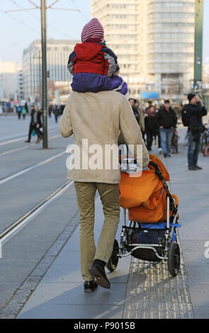 Berlin, Germany, man carries his child on the shoulders and pushes a stroller - Stock Photo