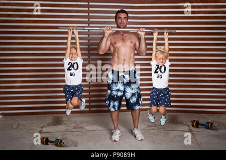 funny heavy lifting photo, Man lifting twins as weights, - Stock Photo