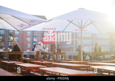 BREMEN, GERMANY - MARCH 23, 2016: Tourist having a beer in a restaurant on an embarktment of Weser river in Bremen - Stock Photo