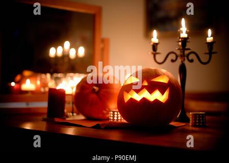 Group of spooky Halloween jack-o-lanterns lit at night - Stock Photo