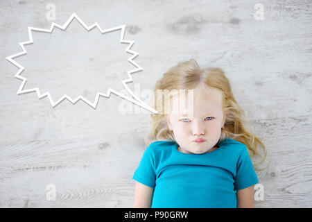Funny little girl lying on white wooden floor with a speech bubble above her head - Stock Photo