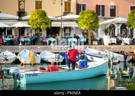 DESENZANO DEL GARDA, ITALY - SEPTEMBER 23, 2016: Fisherman in a boat in Desenzano del Garda, a town and comune in the province of Brescia, in Lombardy - Stock Photo
