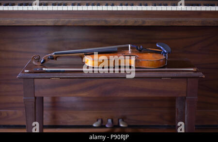 Vintage Violin and Bow Laying on Bench with Piano in Background
