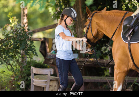 Young preparing  a horse for a ride - Stock Photo