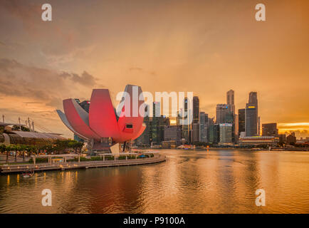 Singapore skyline  under an orange sky as a thunderstorm begins, with the Art and Science Museum illuminated in pink. Architect was Moshe Safdie. - Stock Photo
