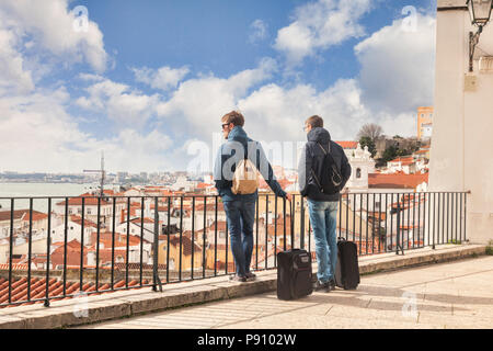 7 March 2018: Lisbon, Portugal - Two young males with carry on luggage looking at the view of the city from Miradouro de Santa Estevao. - Stock Photo