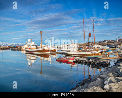 13 April 2018: Husavik, Iceland. The harbour at Husavik in Northern Iceland, with boats, including whale-watching vessels, reflected in the calm water