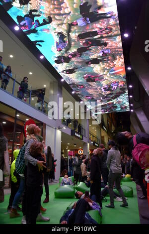 Sydney Australia - May 25, 2018. People walk under the giant screen (Skyportal) and see themself mirrored above, transported to another time and place - Stock Photo
