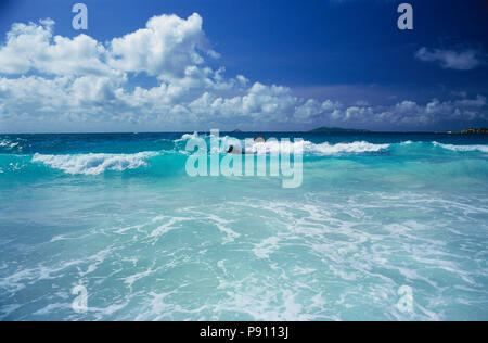 WAVES BREAKING ON BIRD ISLAND AND ISLAND VIEW, SEYCHELLES, ISLAND, EAST AFRICA. JUNE 2009. The beautiful islands of the Seychelles in the Indian Ocean - Stock Photo