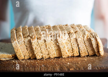 Woman holding gluten free bread with chickpea, linseed, oat, potato, rye flour on wooden board - Stock Photo