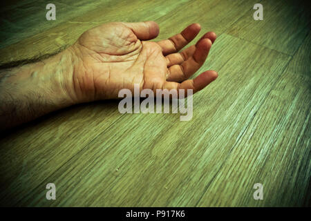 male hand and arm lying on the floor, dead - Stock Photo