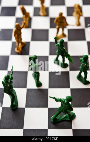 two armies of plastic toy soldiers facing each other on a checkerboard - Stock Photo