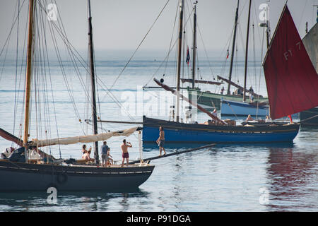 Mousehole, Cornwall, UK. 14th July 2018. UK Weather. The sea was calm and it was hot early in the morning for these visting yachts to the Mousehole Sea Salts and Sail festival which is on over the weekend. Some even took to walking the 'plank' and jumping into the sea for an early morning dip. Credit: Simon Maycock/Alamy Live News - Stock Photo