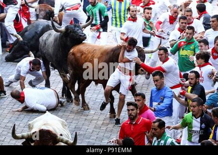 'Mozos' or runners are chased by several bulls during the eight and last San Fermin bull run in Pamplona, Spain, 14 July 2018. The 400-year-old annual festival, held from 06 to 14 July every year, honors the city's patron saint, San Fermin, and attracts thousands of tourists for a nine-day party punctuated by the daily running of bulls through city streets and bullfights. EFE/Rodrigo Jimenez - Stock Photo