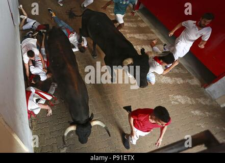 Several runners are chased by bulls in the access of the bullring during the eight and last San Fermin bull run in Pamplona, Spain, 14 July 2018. The 400-year-old annual festival, held from 06 to 14 July every year, honors the city's patron saint, San Fermin, and attracts thousands of tourists for a nine-day party punctuated by the daily running of bulls through city streets and bullfights. EFE/Josu Santesteban - Stock Photo
