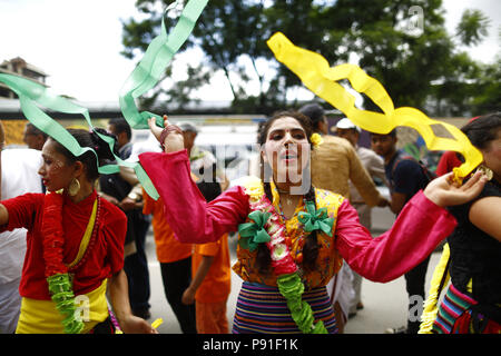 Kathmandu, Nepal. 14th July, 2018. Devotees dressed in traditional attire dance and sing during a procession held to celebrate Jagannath Rath Yatra, a chariot festival in Kathmandu, Nepal on Saturday, July 14, 2018. This procession is a replica of the famous Jagannath Rath Yatra held annually in Jagannath Puri, Odisha since 10th-11th century. Ratha Yatra is a festival that involves moving deities Jagannath, Balabhadra, Subhadra and Sudarshana on a chariot. Credit: Skanda Gautam/ZUMA Wire/Alamy Live News - Stock Photo
