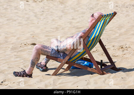 Bournemouth, Dorset, UK. 14th July 2018. UK weather: The heatwave continues with another hot sunny day, as sunseekers make the most of the glorious weather and head to the seaside at Bournemouth beaches. Man sunbathing in deckchair. Credit: Carolyn Jenkins/Alamy Live News - Stock Photo