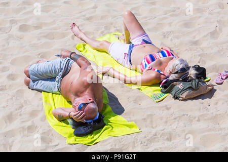 Bournemouth, Dorset, UK. 14th July 2018. UK weather: The heatwave continues with another hot sunny day, as sunseekers make the most of the glorious weather and head to the seaside at Bournemouth beaches. Couple sunbathing on beach. Credit: Carolyn Jenkins/Alamy Live News - Stock Photo