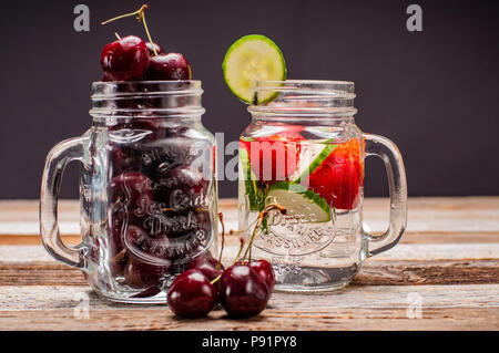 Two glass jars of fresh cherries and water with fruit on wooden table. - Stock Photo