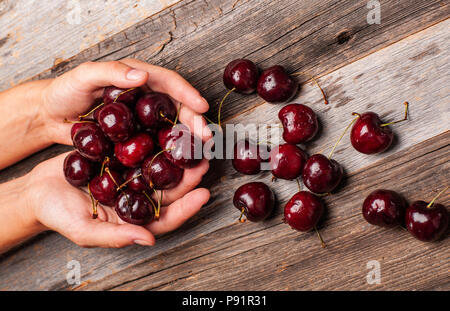Woman is holding fresh cherries in hands. Cherry on wood table - Stock Photo