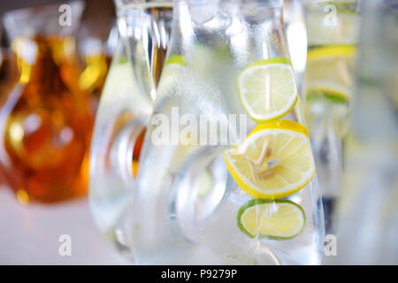 Jugs full of refreshing lime drink on some festive event or catered dinner - Stock Photo