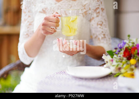 Woman in white dress drinking hot ginger tea on beautiful summer day - Stock Photo