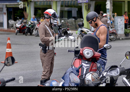 Thailand traffic police with officer issuing a violation ticket to offending motorcycle rider - Stock Photo