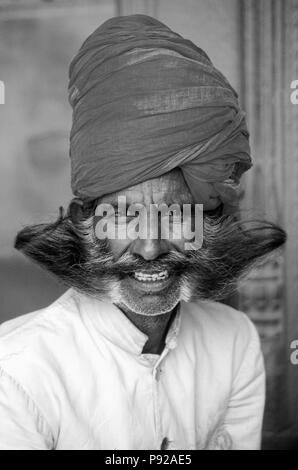 GUARD with RED TURBAN and 'soup-strainer' MUSTACHE and BEARD at the CITY PALACE in JAIPUR - RAJASTHAN, INDIA  - Stock Photo