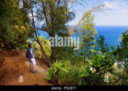 Young male tourist hiking on beautiful Pololu loop trail located near Kapaau, Hawaii, that features beautiful wild flowers and stunning views to the P
