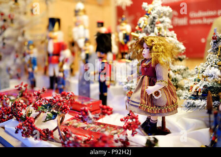 Christmas doll sold at Christmas market in Vilnius, Lithuania. Decorated and illuminated shopping stands with variety of Xmas toys. - Stock Photo
