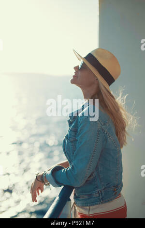 Blonde traveler woman in hat daydreaming on cruise ship Stock Photo