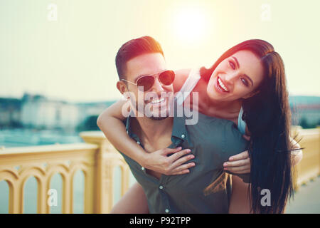 Happy couple outdoors in city sunset, woman doing piggyback - Stock Photo