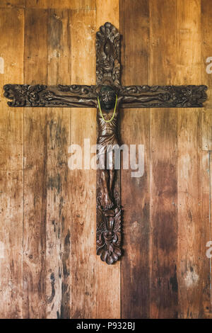 Carved figure of Jesus hanging on wooden background wall - Stock Photo