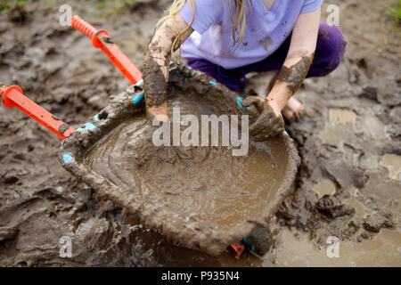 Funny little girl playing in a large wet mud puddle on sunny summer day. Child getting dirty while digging in muddy soil. Messy games outdoors. - Stock Photo