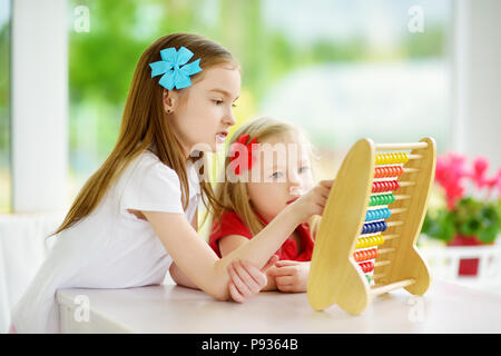 Two cute little girls playing with abacus at home. Big sister teaching her sibling to count. Smart child learning to count. Preschooler having fun wit - Stock Photo