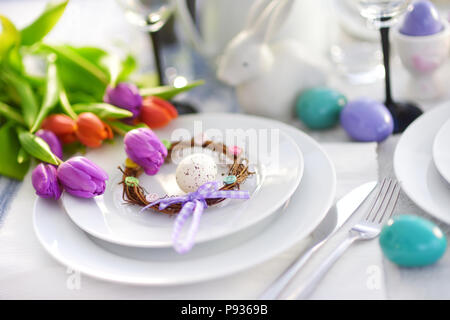 Beautiful table setting with crockery and flowers for Easter celebration. Glassware and cutlery for catered event dinner. - Stock Photo