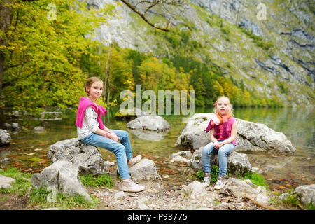 Little girls enjoying the view of deep green waters of Obersee, located near Konigssee, known as Germany's deepest and cleanest lake, Bavaria, Germany - Stock Photo