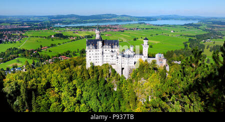 Famous Neuschwanstein Castle, 19th-century Romanesque Revival palace on a rugged hill above the village of Hohenschwangau near Fussen in southwest Bav - Stock Photo