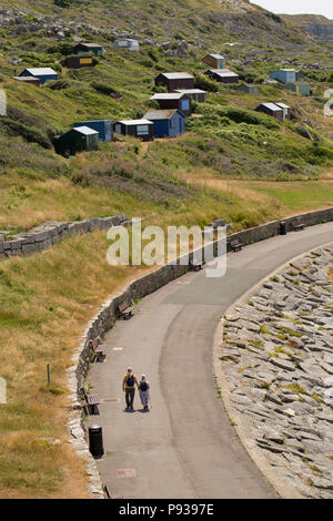 Two people on a sunny day walking next to Chesil Cove with beach huts on the Isle of Portland in the background. Chesil cove is the eastern most point - Stock Photo