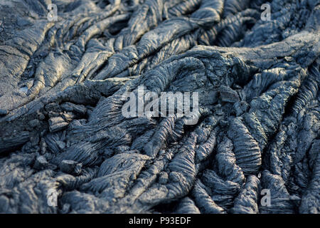 Smooth, undulating surface of frozen pahoehoe lava. Frozen lava wrinkled in tapestry-like folds and rolls resembling twisted rope on Big Island of Haw - Stock Photo