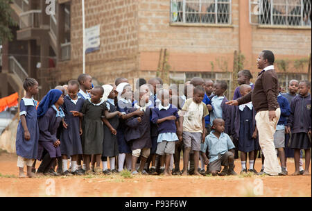 Nairobi, Kenya - Students in school uniforms lined up in front of a teacher in the courtyard of St. John's Community Center Pumwani. - Stock Photo