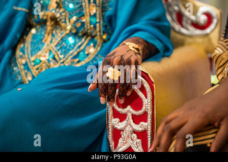 Black and Brown Henna Hands Drawings on Women for African Wedding Ceremony with Gold Ring - Stock Photo