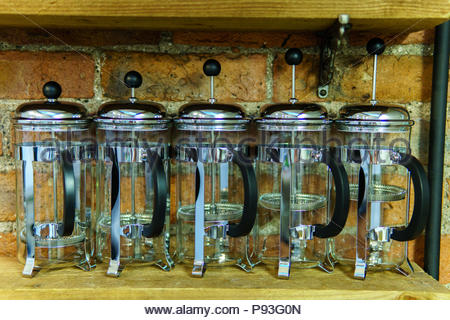 Five glass tea pots on a wooden shelf - Stock Photo