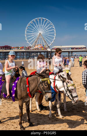 UK, England, Lancashire, Blackpool, children preparing for donkey ride on beach near South Pier - Stock Photo