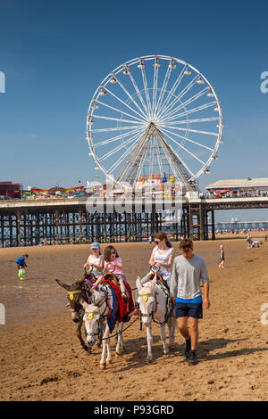 UK, England, Lancashire, Blackpool, children enjoying donkey ride on beach near South Pier - Stock Photo