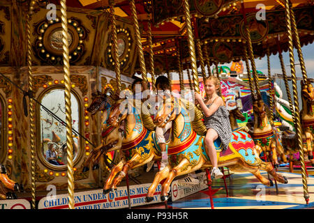 UK, England, Lancashire, Blackpool, South Pier, children riding on traditional fairground carousel horses - Stock Photo