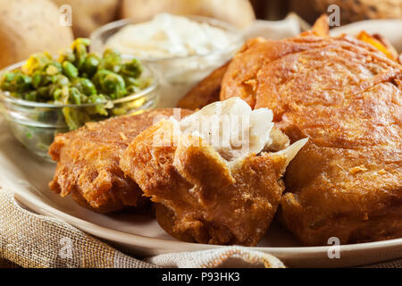 Traditional fish in beer batter and chips with green pea and tartar sauce - Stock Photo