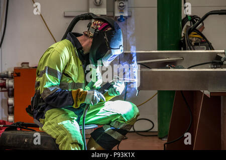 Welder wearing protective equipment welding - Stock Photo